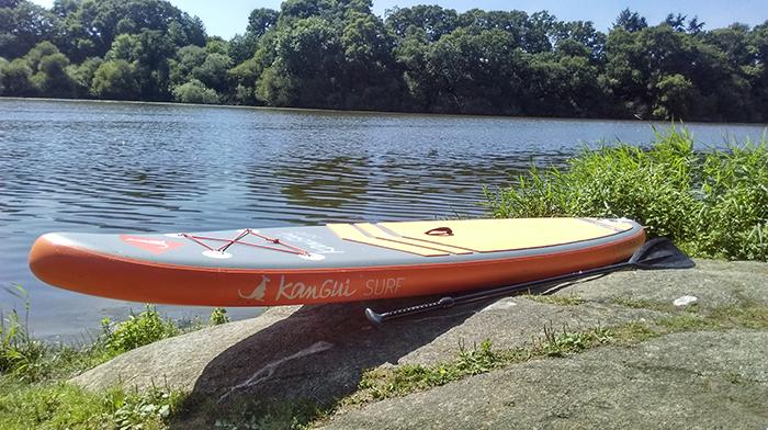 stand up paddle gonflable bali posé le long d'une rivière